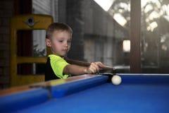 Pojke som spelar pölen arkivbilder