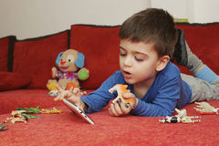 Pojke som spelar på minnestavlan, inomhus Arkivbild