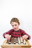 Pojke som spelar schack med honom, ståendestudioskott royaltyfri foto
