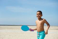 Pojke som spelar skovelbollen på stranden Royaltyfri Bild