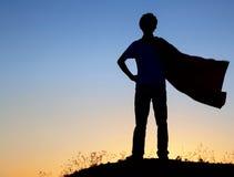 Pojke som spelar superheroes på himmelbakgrunden, kontur av utslagsplatsen Arkivfoton