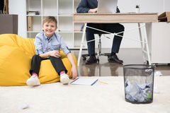 Pojke som spelar trashketball medan hans fader som arbetar på kontoret Fotografering för Bildbyråer