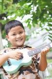 Pojke som spelar ukulelet Arkivbilder