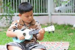 Pojke som spelar ukulelet Arkivbild