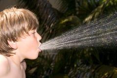 pojke som spottar vatten Fotografering för Bildbyråer