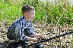 Pojke som Squatting på den hållande metspöet för flodstrand Royaltyfri Foto