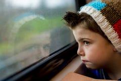 Pojke som stirrar till och med fönster Royaltyfria Bilder