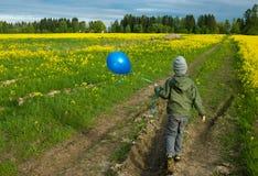 Pojke som stöter ihop med fältet med en ballong Arkivfoto