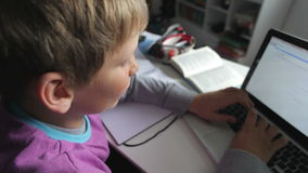 Pojke som studerar i sovrum genom att använda bärbara datorn stock video