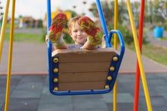 Pojke som svänger på en gunga i lekplatsen Arkivbild