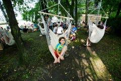 Pojke som svänger i en hängmatta på ett träd på det utomhus- partiet Arkivbild