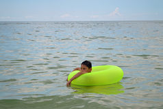 Pojke som svävar i uppblåsbar cirkel Fotografering för Bildbyråer