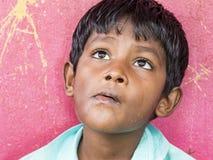 Pojke som tänker och ser upp över rosa bakgrund royaltyfria foton