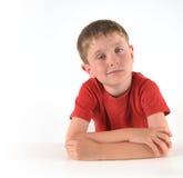 Pojke som tänker om fråga på vit bakgrund Royaltyfria Bilder
