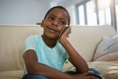 Pojke som talar på mobiltelefonen i vardagsrummet Royaltyfria Foton