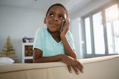 Pojke som talar på mobiltelefonen i vardagsrummet Arkivfoto