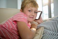 Pojke som talar på mobiltelefonen i vardagsrummet Arkivbilder