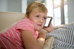 Pojke som talar på mobiltelefonen i vardagsrummet Fotografering för Bildbyråer