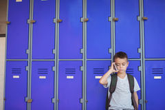 Pojke som talar på mobiltelefonen mot skåp Royaltyfria Bilder