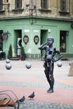 Pojke som talar på mobiltelefonmodern konstskulpturen i Liberty Square av Timisoara Royaltyfri Fotografi