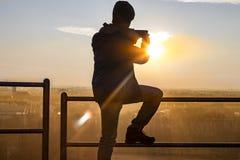 Pojke som tar bilder till en solnedgång royaltyfria bilder