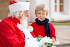 Pojke som tar gåva från Santa Claus Royaltyfri Fotografi