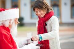 Pojke som tar kex från Santa Claus Fotografering för Bildbyråer