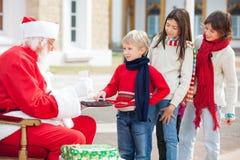 Pojke som tar kex från Santa Claus Royaltyfria Foton