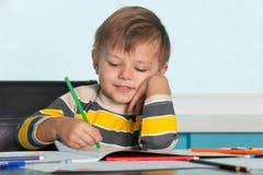 pojke som tecknar little som ler Fotografering för Bildbyråer