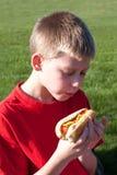 Pojke som äter en varmkorv Arkivbilder