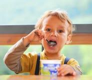 pojke som äter little yoghurt Arkivfoton