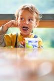 pojke som äter little yoghurt Arkivfoto