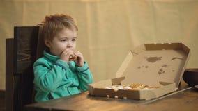 Pojke som ?ter pizza p? en tr?bakgrund smaklig pizza Pys som har en skiva av pizza Hungrigt barn som tar en tugga arkivfilmer