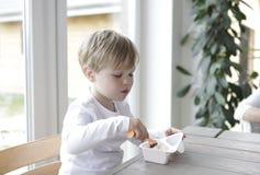 pojke som äter yoghurt Royaltyfri Fotografi