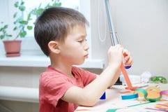 Pojke som tillverkar med pappers- sammanträde på tabellen, tidig hjärnframkallning arkivbilder