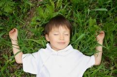 Pojke som tycker om att ligga ner på gräset Royaltyfri Foto