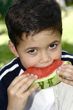 pojke som tycker om den saftiga röda vattenmelonen Fotografering för Bildbyråer