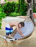 Pojke som tycker om en hammoc på den härliga tropiska stranden Arkivbilder