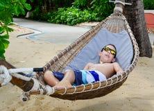 Pojke som tycker om en hammoc på den härliga tropiska stranden Royaltyfri Fotografi