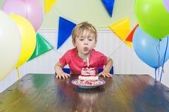 Pojke som ut blåser en födelsedagstearinljus Arkivbild