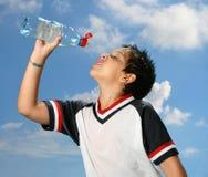 pojke som ut dricker törstigt vatten royaltyfri bild