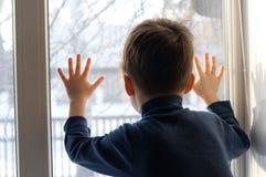 pojke som ut ser fönstret royaltyfri bild