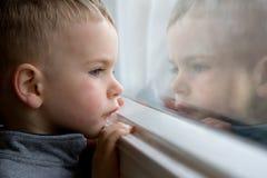pojke som ut ser fönstret Royaltyfri Fotografi