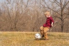 Pojke som utanför sparkar bollen Arkivbilder