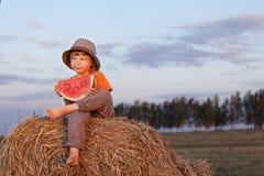 Pojke som utomhus äter vattenmelon royaltyfria foton