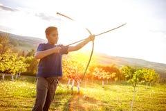 Pojke som utomhus siktar den hemlagade träpilbågen arkivfoto