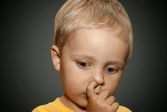 Pojke som väljer hans näsa Arkivfoto