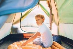 Pojke som vilar i campa tält och att tycka om med solnedgångljus i bergdalen arkivfoton