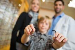 Pojke som visar exponeringsglas med modern och optiker In royaltyfri fotografi