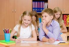 Pojke som viskar hemligheter av flickan i klassrumet Arkivfoton